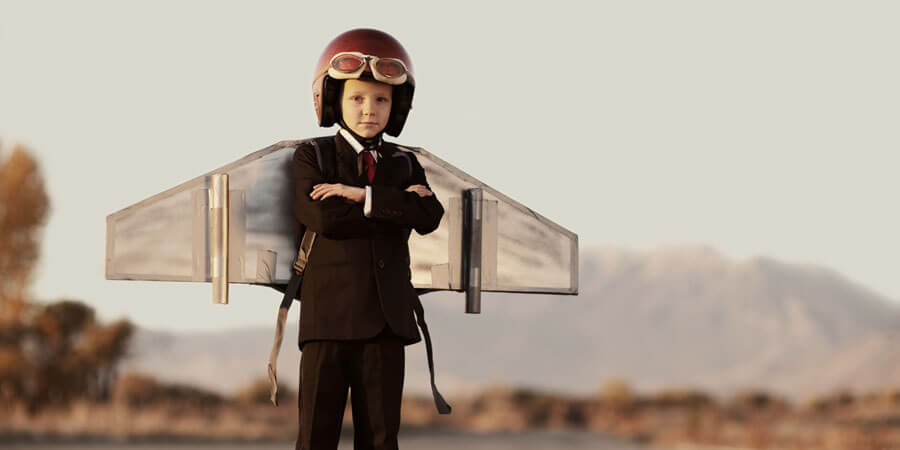 Child wearing a suit and a helmet with flight gogles and wings on their back